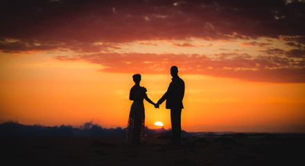 couple lover holding hand on the beach during sunrise morning sky