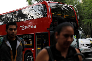 Pedestrians walk past one of dozens of British double-decker buses, which is part of a one billion peso deal with Britain to help the sprawling capital tackle traffic and pollution in Mexico City