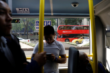 Commuters ride on one of dozens of British double-decker buses, part of a one billion peso deal with Britain to help the sprawling capital tackle traffic and pollution in Mexico City, Mexico