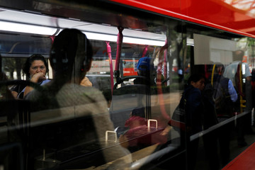 Commuters ride on one of the dozens of British double-decker buses, part of a one billion peso deal with Britain to help the sprawling capital tackle traffic and pollution in Mexico City, Mexico