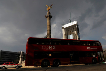 One of the dozens of British double-decker buses, which is part of a one billion peso deal with Britain to help the sprawling capital tackle traffic and pollution, moves past the Angel of Independence monument in Mexico City, Mexico