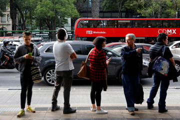 Commuters wait in a queue while a British double-decker bus, which is one of dozens of brought to the sprawling capital as part of a one billion peso deal with Britain to help tackle traffic and pollution, is seen in the background in Mexico City, Mexico