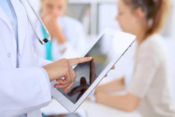 Doctor using tablet computer, close-up of hands at touch pad screen