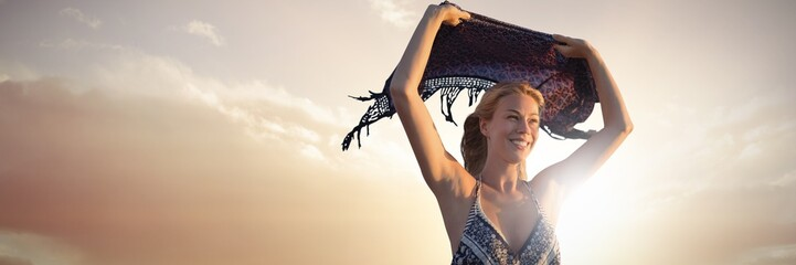 Composite image of smiling woman holding scarf in the air