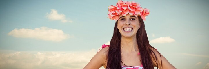 Composite image of smiling woman holding wreath of flowers