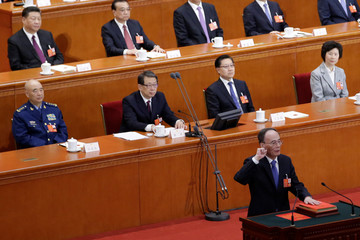 Newly elected Chinese Vice President Wang Qishan with his hand on the Constitution takes the oath at the fifth plenary session of the National People's Congress (NPC) at the Great Hall of the People in Beijing