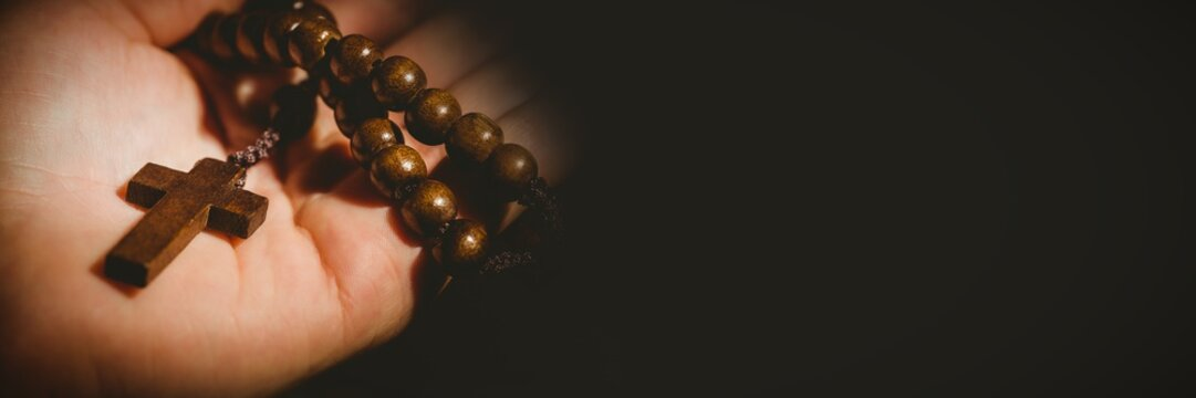 Hand holding rosary beads