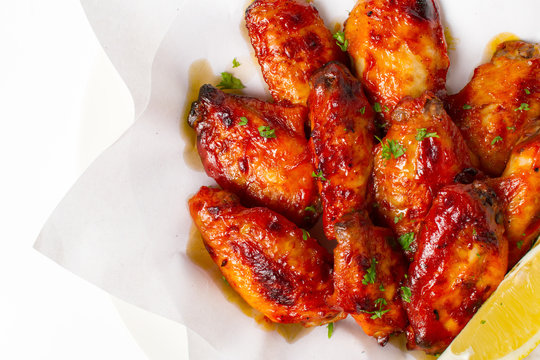 Grilled chicken wings with BBQ sauce. Garnish with lemon and coriander in a paper top view closeup on white background