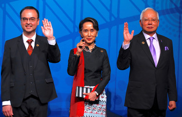 Myanmar's State Counsellor Aung San Suu Kyi waves with Philippines' Secretary of Foreign Affairs Alan Peter Cayetano and Malaysia's Prime Minister Najib Razak during the Leaders Welcome and Family Photo at the the one-off ASEAN summit in Sydney