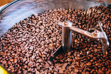 roasted coffee beans, over a modern machine used for roasting beans, can be used as a background