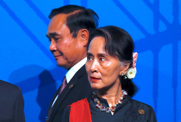 Thailand's Prime Minister Prayut Chan-O-Cha walks behind Myanmar's State Counsellor Aung San Suu Kyi as they prepare for the Leaders Welcome and Family Photo during during the one-off ASEAN summit in Sydney