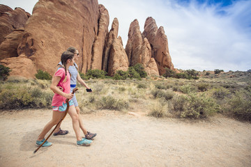 Two happy girls hiking together in the beautiful rock cliffs of Arches National Park. Walking along a scenic trail with large rock formations behind them