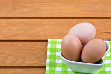 Eggs in a porcelain bowl on a wooden background