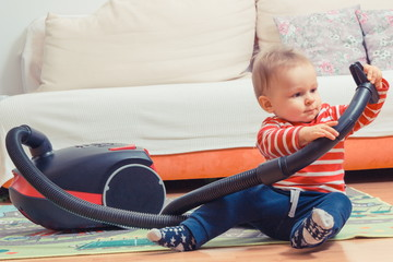 Little baby boy sitting on carpet and playing with pipe of vacuum cleaner with brush