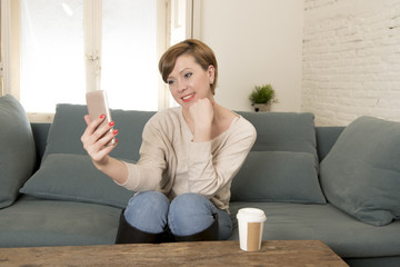 young attractive and happy red hair woman sitting at home sofa couch drinking coffee taking selfie picture with mobile phone camera