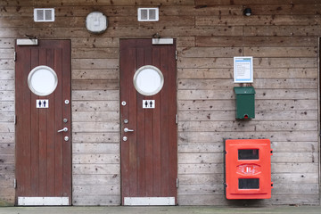 Campsite public park toilets male and female doors signs brown wooden