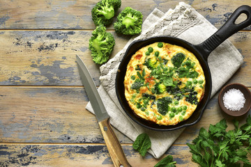 Spring omelette with green vegetables (broccoli, sweet pea and spinach) in a skillet.Top view.