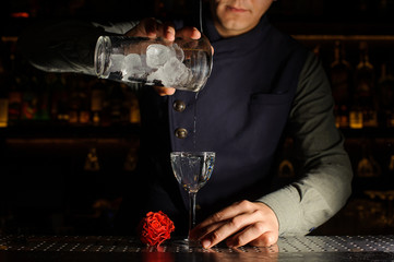Barman pouring a fresh alcoholic drink into a glass
