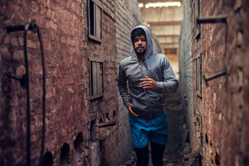 Portrait of focused motivated afro-american young handsome runner hooded man with earphones jogging inside of the abandoned place in the middle of two walls.