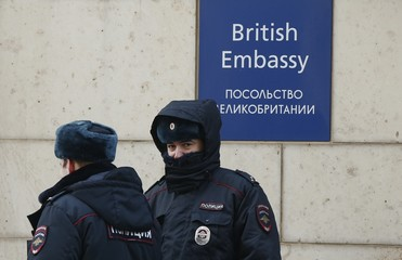 Russian policemen walk outside the British embassy in Moscow