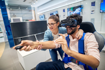 Young cute playful love couple having fun with VR goggles in the tech store.