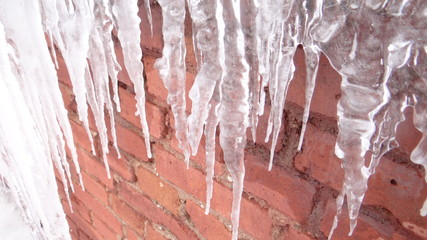 Icicles on a brick wall background.