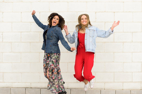 Two young happy women jumping outdoors