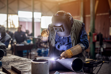 Profesional welder in protective uniform and mask welding metal pipe on the industrial table with other workers behind in the industrial workshop.