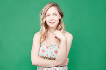 Charming playful coquettish young European female with wavy hair smiling shyly at camera, flirting. Pretty lady with green eyes and cute face having joyful expression, posing over green studio wall.