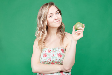 Healthy food and lifestyle concept. Pretty female eats fresh apple, thinks about new diet, being glad to loose weight. Caucasian woman poses in light summer dress over green wall studio background.