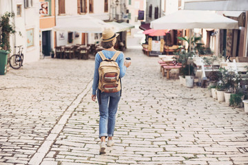Tourist girl walking in the city during vacation. Cheerful woman traveling abroad in summer. Travel and active lifestyle concep