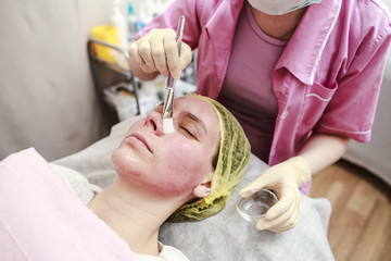 Professional - beautician puts on the skin for the chemical peeling agent with a brush, close-up.