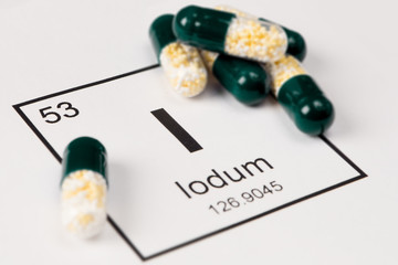 Green pills with mineral I (Iodium) on a white background with an inscription from the chemical table