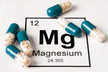 pills with mineral Mg (magnesium) on a white background with an inscription from the chemical table