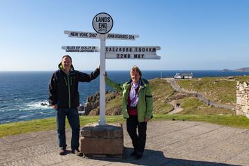 Touristen Frau und Mann mit Wegweiser von Lands End nach Salzburg in Cornwall