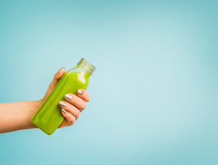 Wall Murals Juice Female hand holding bottle with green summer beverage: smoothie or juice at blue background.