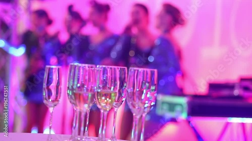 Glasses with champagne on the background of silhouettes of women's