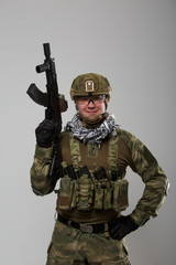 Photo of soldier in safety glasses with gun in his hand
