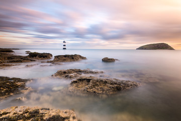 Wide angle view of Penmon Point Lighthouse at sunrise with pink clouds and rocks in foreground.
