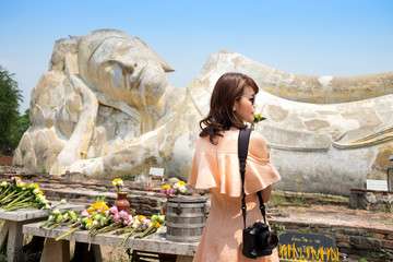 Beautiful Asian woman Worship Buddha statue with incense stick and lotus flower and Psalms Thai Language Stand at Ayutthaya Thailand.