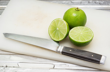 fresh green lime fruit with section on plastic chopping block with a knife at kitchen