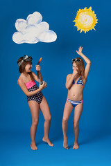 Beautiful 2 girlfriends in swimsuits fun, dance and show joy emotions.Portrait two children,diving mask,image sun,cloud, isolated blue background.Cheerful two sisters rest beach, summer vacation.