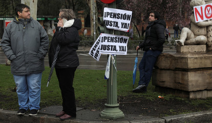 """People stand next to placards reading """"Fair Pension Now"""" at the end of a demonstration demanding higher state pensions, in Madrid"""