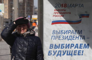 A woman walks a board informing of the upcoming presidential election in Moscow