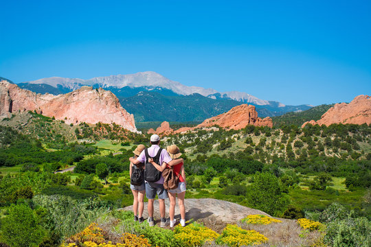 Happy family with arms around each other enjoying beautiful mountain view on  hiking trip. Beautiful red mountains and green hills in Colorado. Garden of the Gods, Colorado Springs, Colorado,  USA.