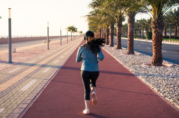 Girl jogging on the running track by the sea