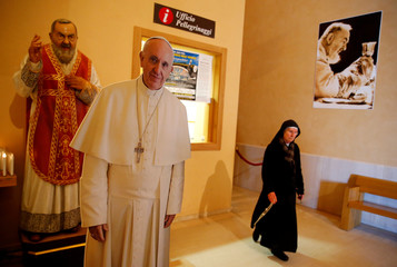 A nun walks past a figure depicting Saint Pio of Pietrelcina (Padre Pio) and Pope Francis in San Giovanni Rotondo