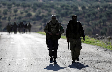 Turkish-backed Free Syrian Army fighters walk after advancing north of Afrin
