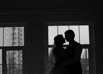 bride and groom kiss in the dark room