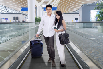 Happy couple wearing white on an airport moving walkway